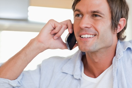 Close up of a smiling man making a phone call looking away from the camera photo