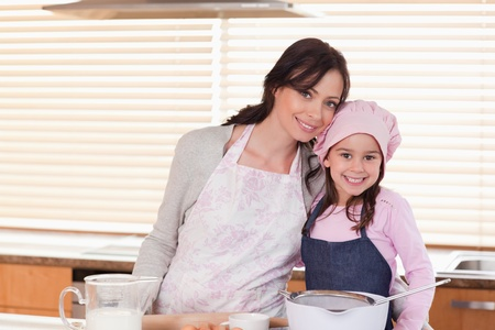 mother board: Mother and daughter baking in a kitchen