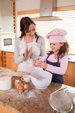 Portrait of a mother teaching her daughter how to bake in a kitchen photo