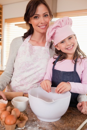 Portrait of a mother baking with her daughter in a kitchen photo