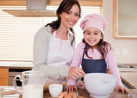 Mother baking with her daughter in a kitchen photo
