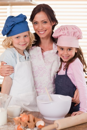 Portrait of a mother and her children baking in a kitchen photo