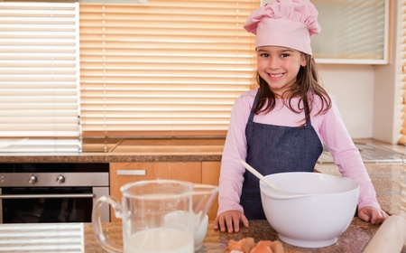 Little girl baking in a kitchen photo