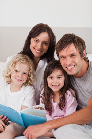 Portrait of a happy family reading a book in a bedroom Stock Photo - 11683372