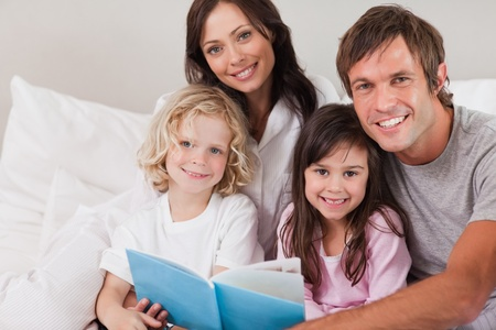Happy family reading a book in a bedroom photo