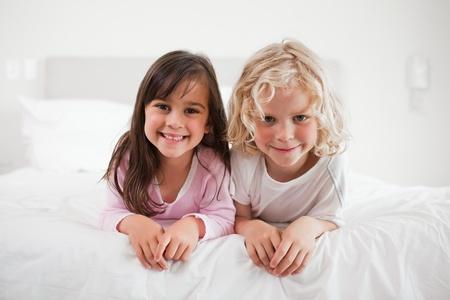 Kinderen liggend op hun buik in een slaapkamer Stockfoto
