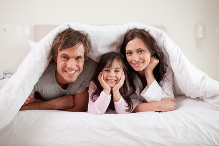 Smiling parents lying under a duvet with their daughter in their bedroom photo