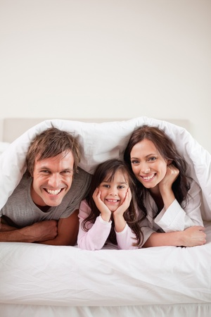 Portrait of parents lying under a duvet with their daughter in their bedroom photo