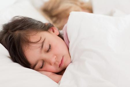 woman sleep: Calmar a los ni�os que dorm�an en un dormitorio Foto de archivo