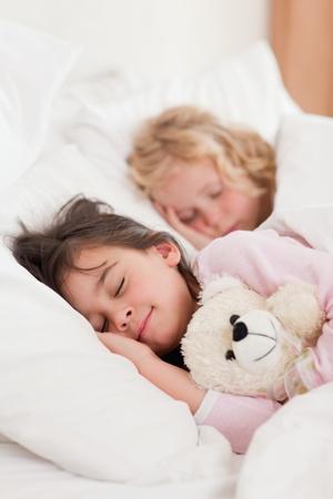 Portrait of siblings sleeping in a bedroom photo
