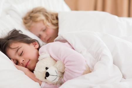 Quiet siblings sleeping in a bedroom photo