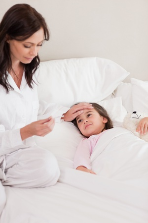 Portrait of a mother checking on her daughters temperature in a bedroom photo