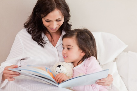 Mother reading a story to her daughter in a bedroom Stock Photo - 11684964