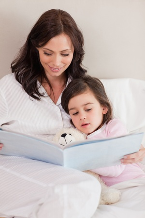 Portrait of a mother reading a story to her daughter in a bedroom Stock Photo - 11685055