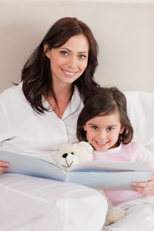 Portrait of a happy mother reading a story to her daughter in a bedroom photo