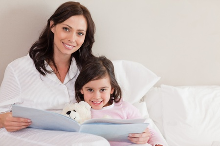 Happy mother reading a story to her daughter in a bedroom Stock Photo - 11685796