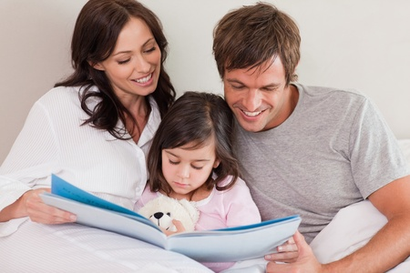 Happy parents reading a story to their daughter in a bedroom Stock Photo - 11682593