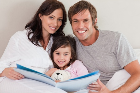 Smiling parents reading a story to their daughter in a bedroom photo