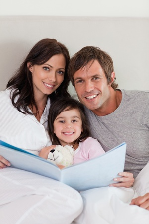 Portrait of parents reading a story to their daughter in a bedroom Stock Photo - 11683279