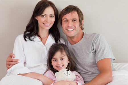 Parents posing with their daughter in a bedroom Stock Photo - 11683809