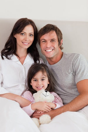 Portrait of parents posing with their daughter in their bedroom Stock Photo - 11684186
