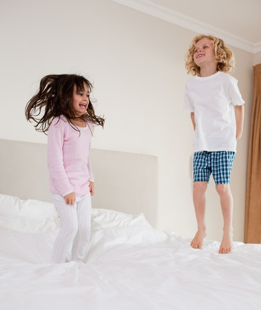 Portrait of children jumping on a bed  photo