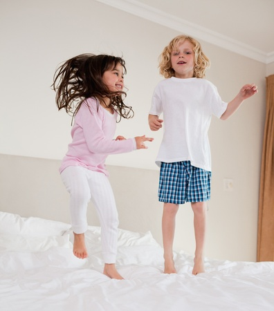 Portrait of siblings jumping on a bed photo