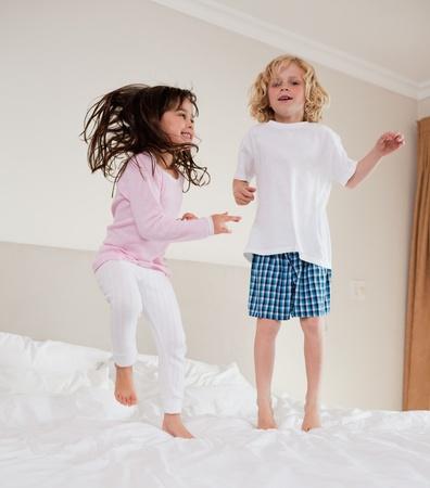 pijama: Retrato de los hermanos de saltar en una cama Foto de archivo