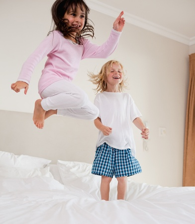 leaping: Portrait of playful siblings jumping on a bed