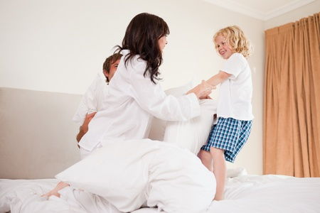 Playful family having pillow fight in a bedroom photo