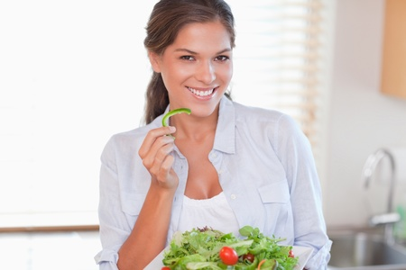 Smiling woman eating a salad in her kitchen photo