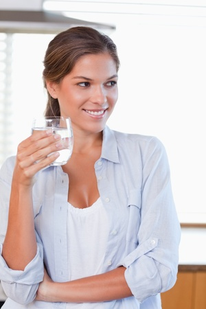 standing water: Portrait of a woman holding a glass of water in her kitchen Stock Photo
