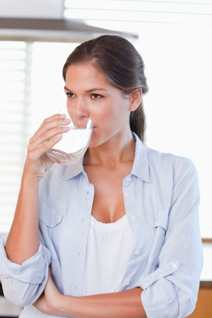 Portrait of a woman drinking a glass of water in her kitchen photo