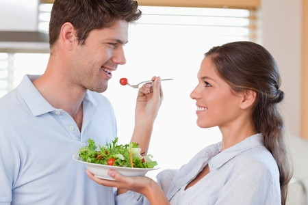 Woman feeding her husband in their kitchen photo