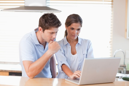 Couple using a laptop in their kitchen photo