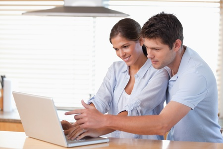 Happy couple using a notebook in their kitchen Stock Photo - 11686188