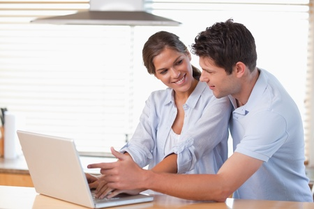 Happy couple using a laptop in their kitchen photo