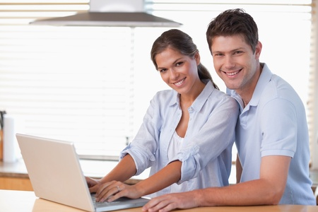 Smiling couple using a laptop in their kitchen photo