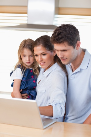 Portrait of a family using a laptop in their kitchen photo