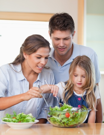 Portrait of a family preparing a salad in their kitchen photo