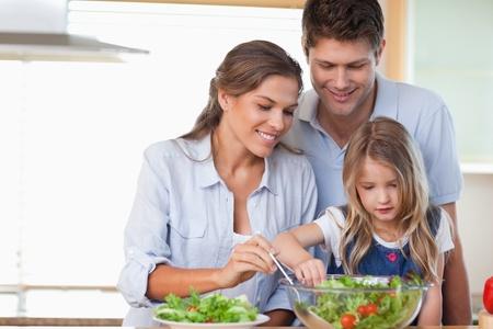 familia saludable: Familia prepara una ensalada en su cocina