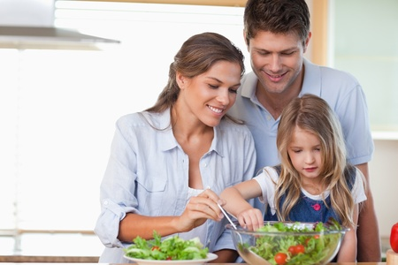 Family preparing a salad in their kitchen photo