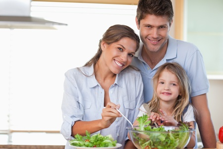 Smiling family preparing a salad in their kitchen photo