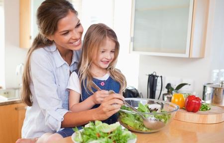 children cooking: Madre y su hija, la preparaci�n de una ensalada en su cocina