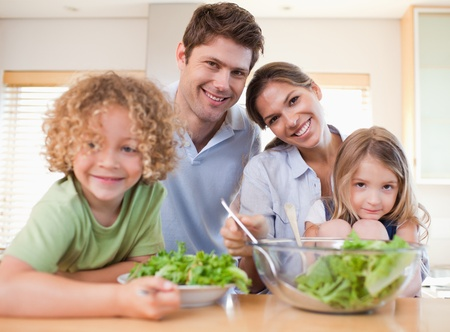 Smiling family preparing a salad together in their kitchen photo