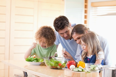 Family preparing a salad together in their kitchen photo