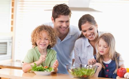 comidas saludables: Familia feliz junto a preparar una ensalada en la cocina