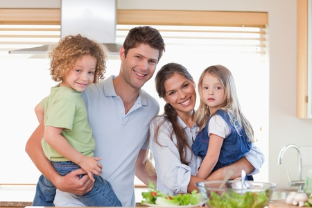 Happy family posing in their kitchen photo