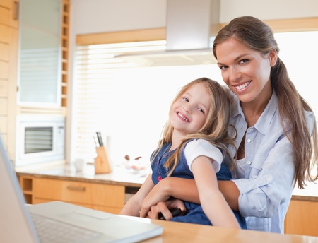 Happy mother and her daughter using a laptop in their kitchen photo