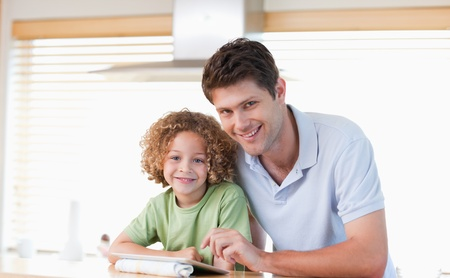 Smiling boy and his father using a tablet computer in their kitchen photo